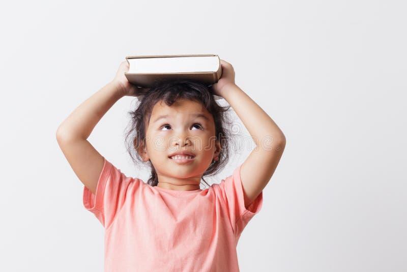 Petite fille asiatique tenant un livre sur la tête et les yeux semblant supérieurs sur la tête blanche de fond Sur le visage une  photographie stock