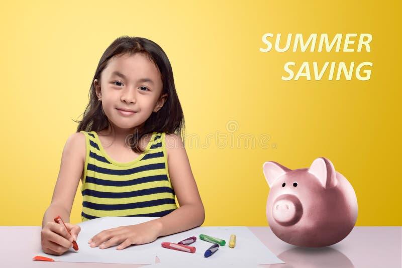 Petite fille assez asiatique avec le crayon et la tirelire sur le bureau photos libres de droits