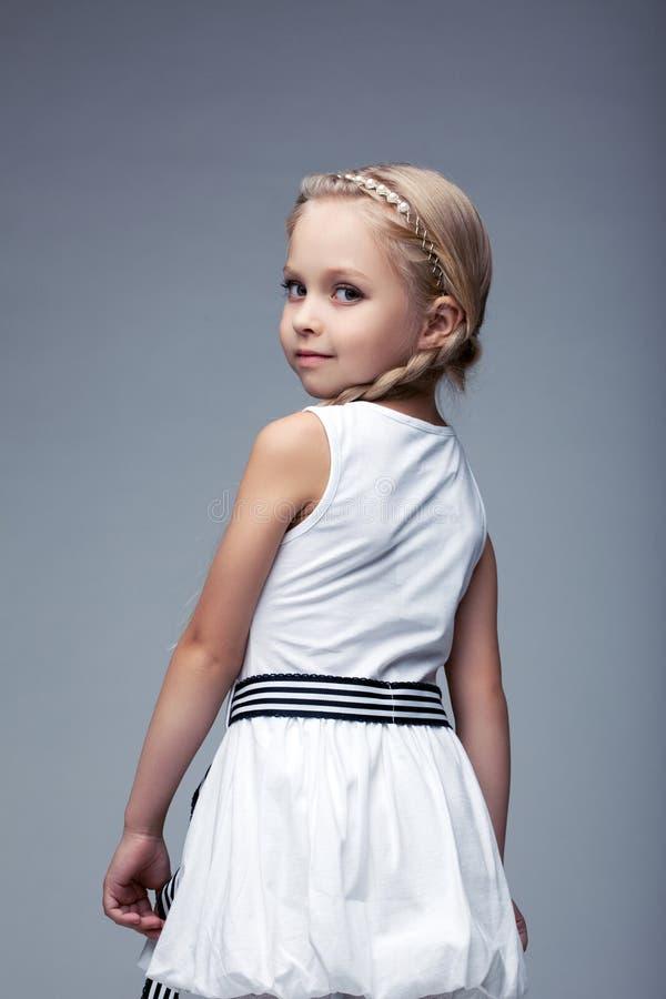 Petite fille assez blonde dans la robe blanche image stock