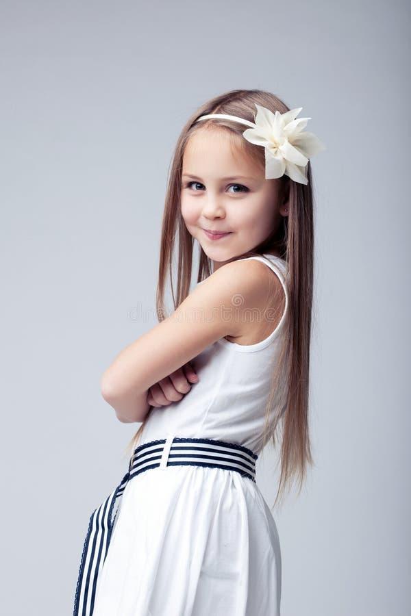 Petite fille assez blonde dans la robe blanche image libre de droits