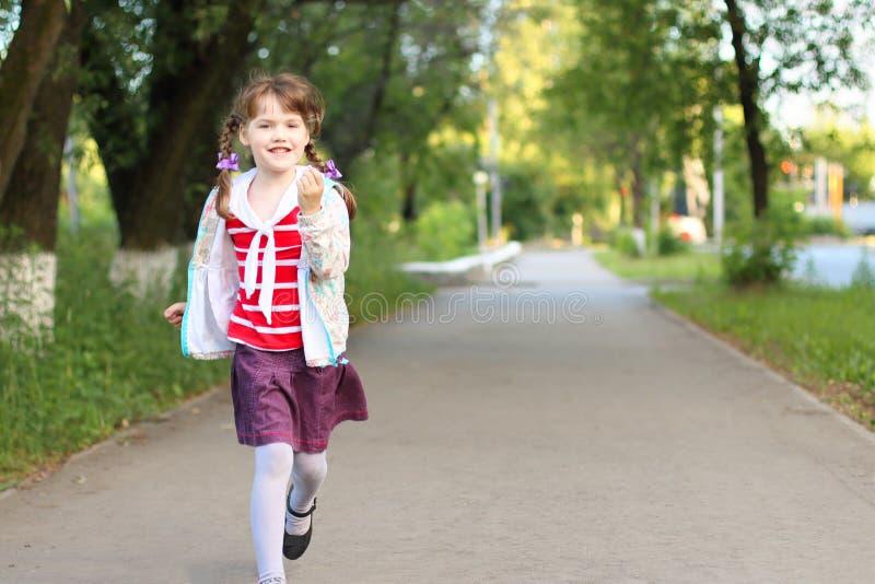 Petite fille assez de sourire avec des courses de tresses photo libre de droits