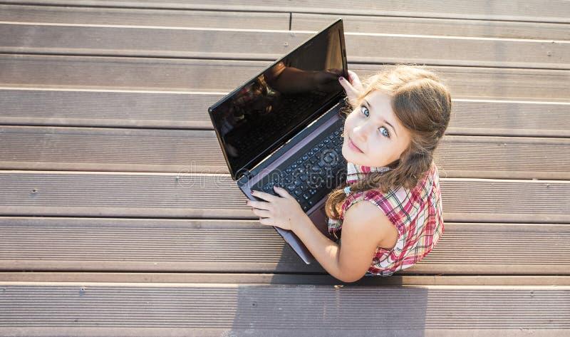 Petite fille assise dans les escaliers et munie d'un ordinateur portable photo libre de droits