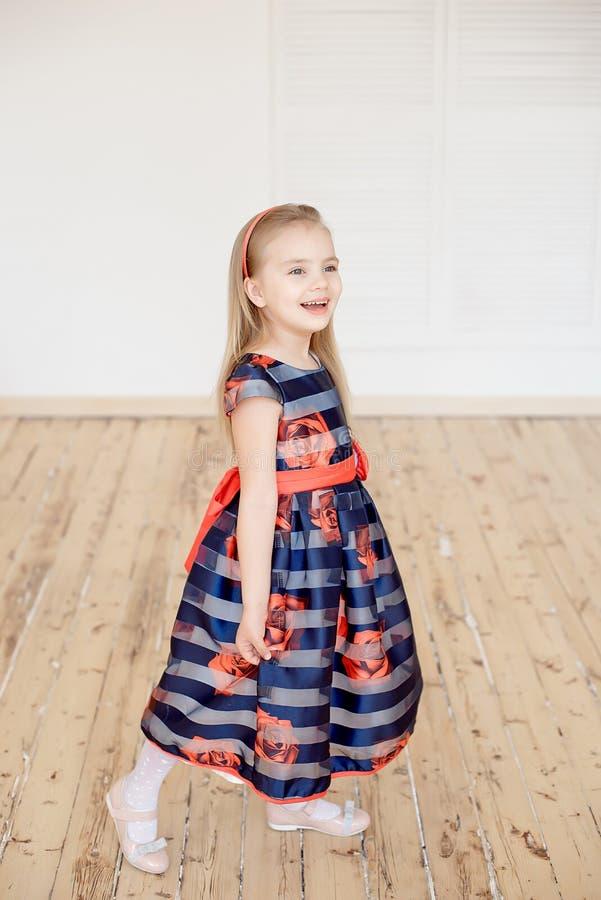 Petite fille attirante dans la robe colorée tournant autour à l'intérieur photo stock