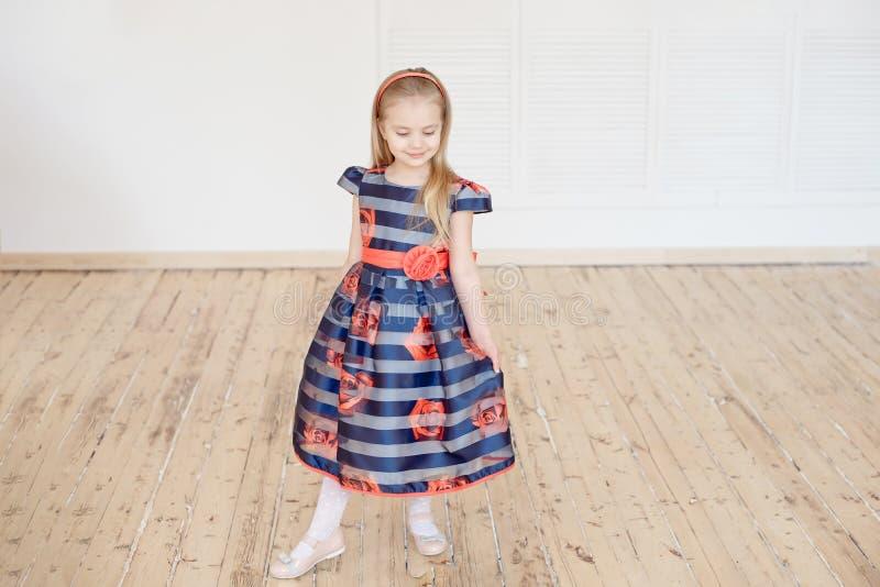 Petite fille attirante dans la robe colorée tournant autour à l'intérieur images libres de droits
