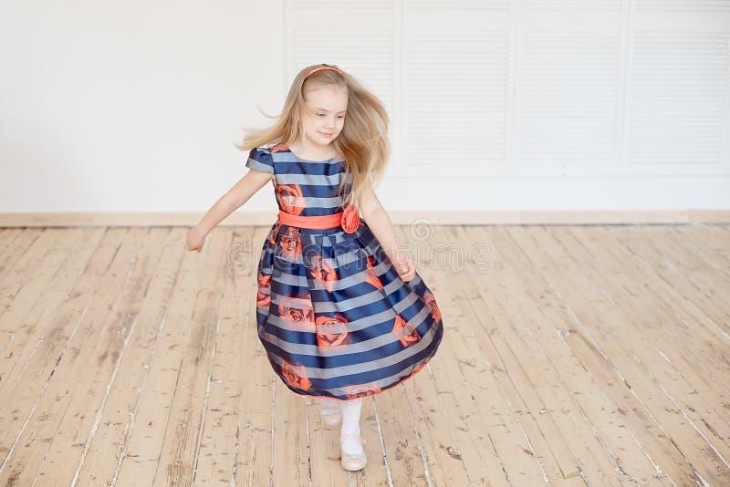 Petite fille attirante dans la robe colorée tournant autour à l'intérieur photographie stock libre de droits