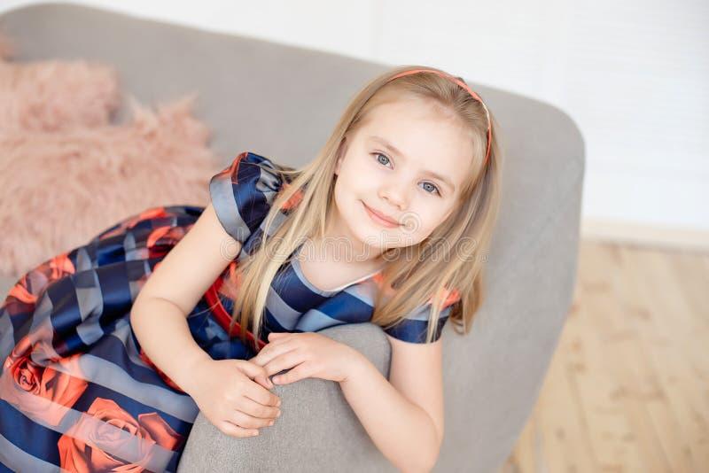 Petite fille attirante dans la robe colorée tournant autour à l'intérieur photos stock