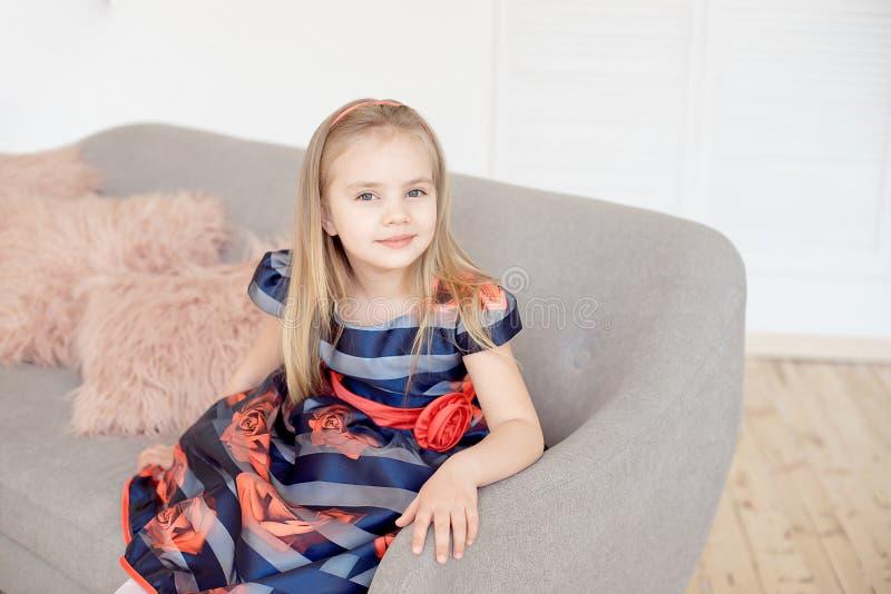 Petite fille attirante dans la robe colorée tournant autour à l'intérieur photos libres de droits