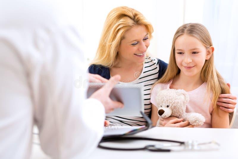 Petite fille au docteur avec sa mère images stock