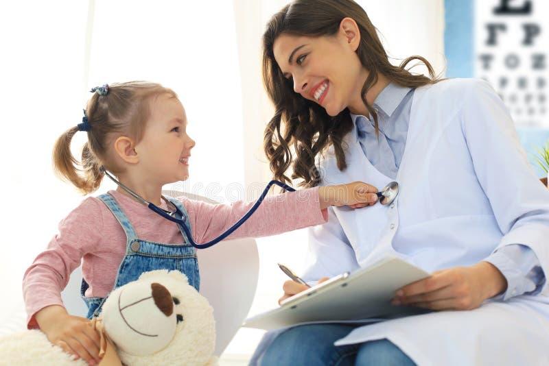 Petite fille au docteur pour un contr?le L'enfant auscultate le battement de coeur du docteur images libres de droits
