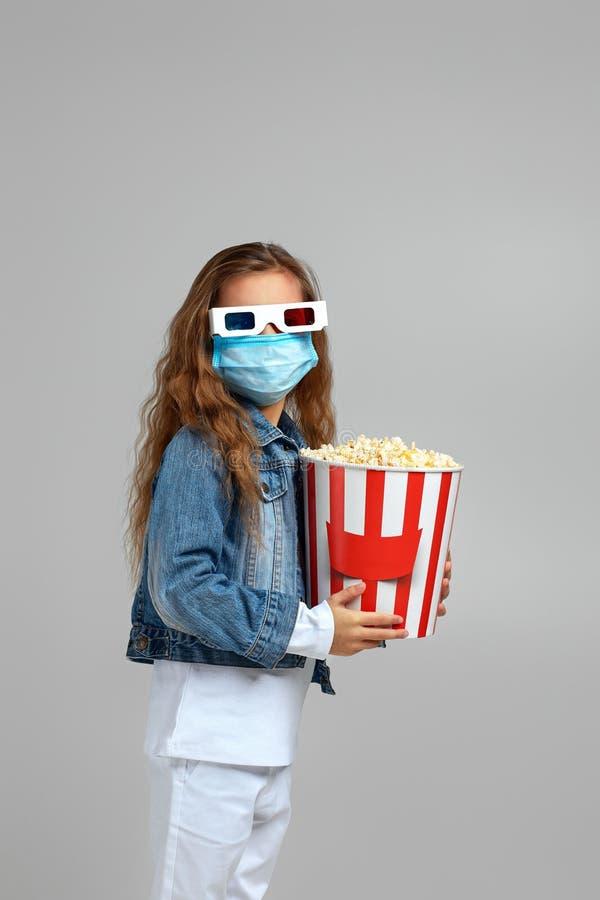 Petite fille au masque tenant un seau à pop-corn photographie stock libre de droits