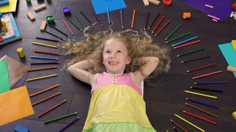 Petite fille aux cheveux blonds de sourire se trouvant sur le plancher et rêvant des vacances photos libres de droits