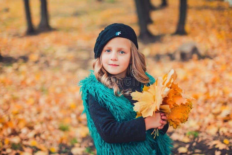 Petite fille aux feuilles de participation d'automne La petite fille dans le béret brun en parc d'automne photo stock