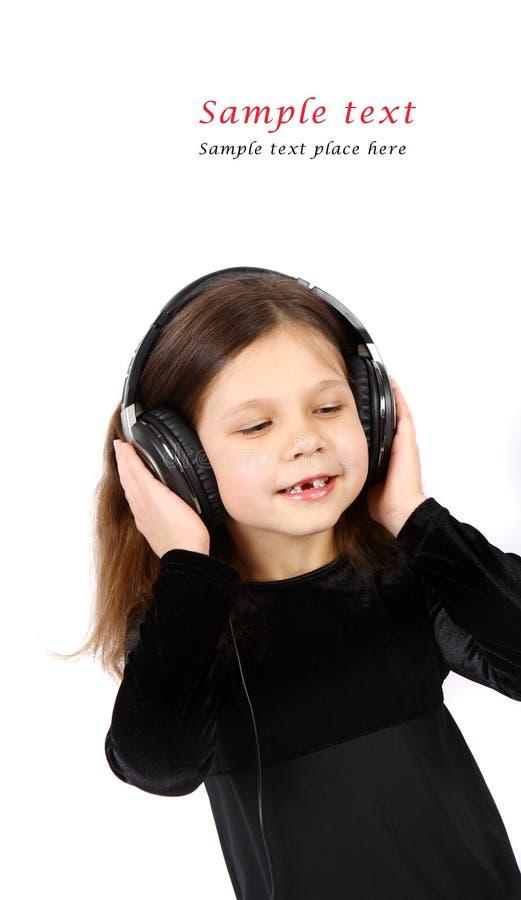 Petite fille avec des écouteurs photographie stock libre de droits