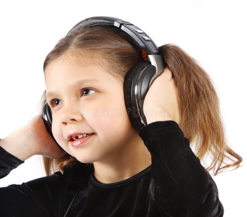 Petite fille avec des écouteurs photo stock