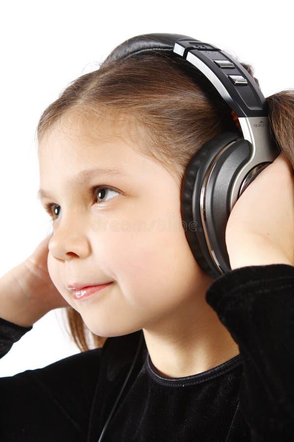 Petite fille avec des écouteurs image stock