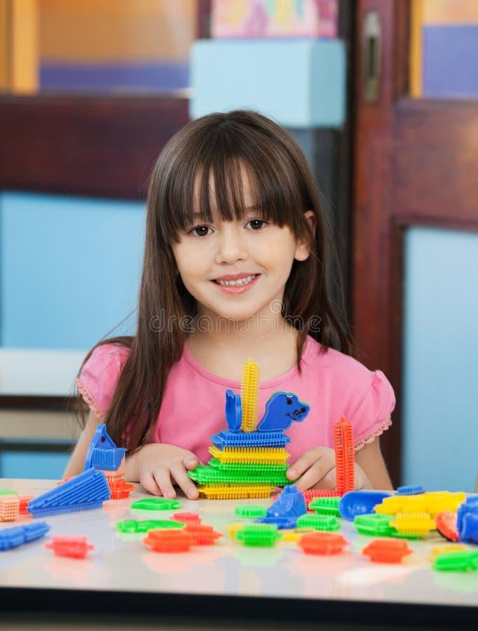 Petite fille avec des blocs de construction dans la salle de classe photographie stock libre de droits