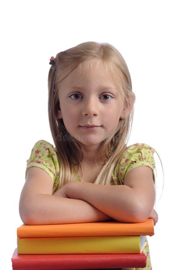 Petite fille avec des bras se reposant sur une pile de livres images stock