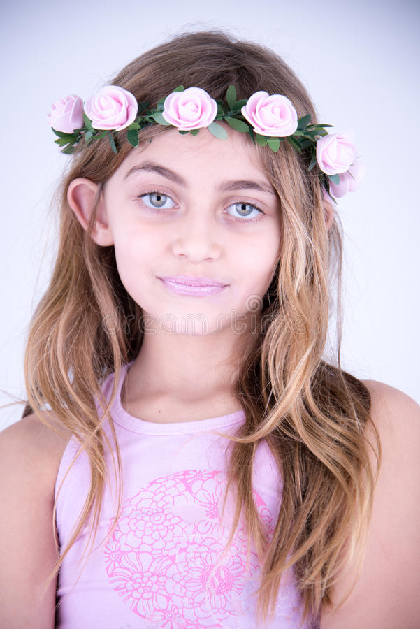 Petite fille avec des fleurs sur la tête image stock