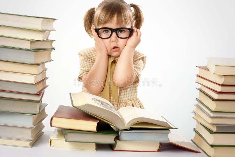 Petite fille avec des livres portant les lunettes noires photos stock