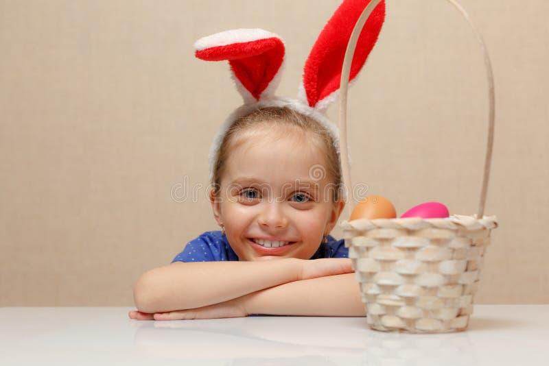Petite fille avec des oeufs de pâques de panier photos stock