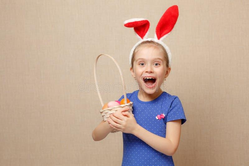 Petite fille avec des oeufs de pâques de panier photographie stock