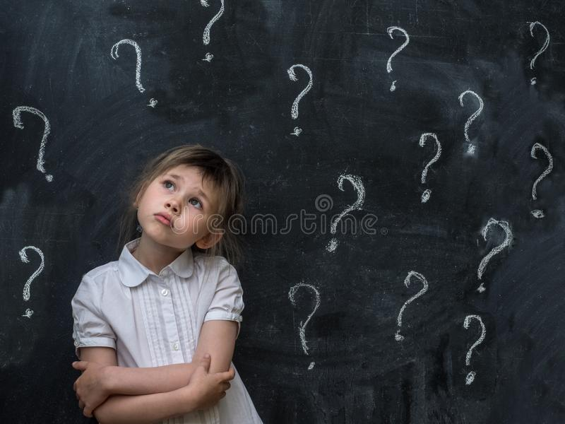 Petite fille avec des points d'interrogation sur le tableau noir Concept pour la confusion, la séance de réflexion et le choix photo stock