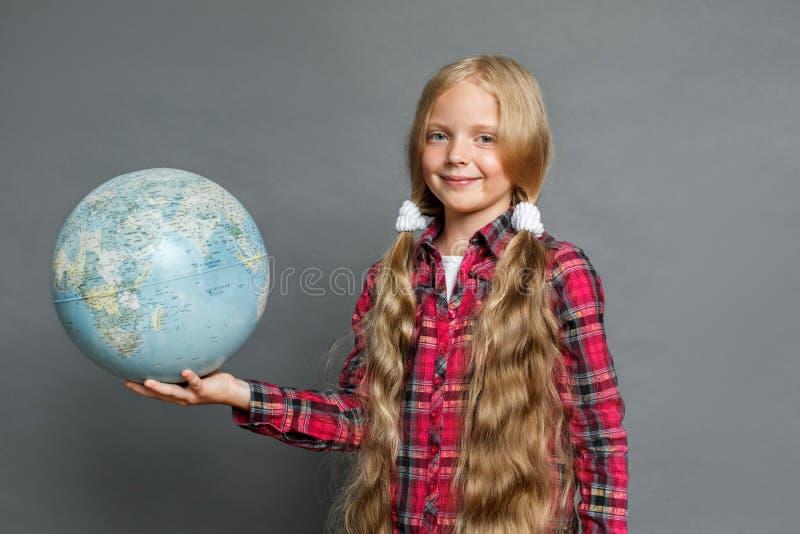 Petite fille avec des queues de cheval se tenant d'isolement sur le gris avec le globe regardant la caméra amicale image stock