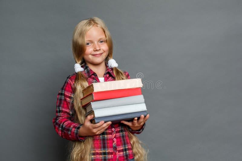Petite fille avec des queues de cheval se tenant d'isolement sur le gris avec la pile des livres regardant la caméra joyeuse image libre de droits