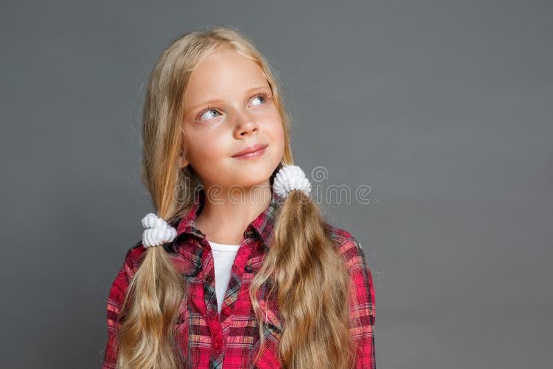 Petite fille avec des queues de cheval se tenant d'isolement sur le gris regardant de côté le plan rapproché dreamful image stock