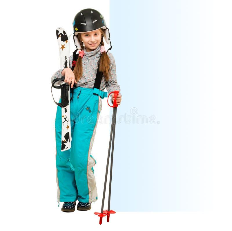 Petite fille avec des skis se dirigeant à un blanc vide photographie stock