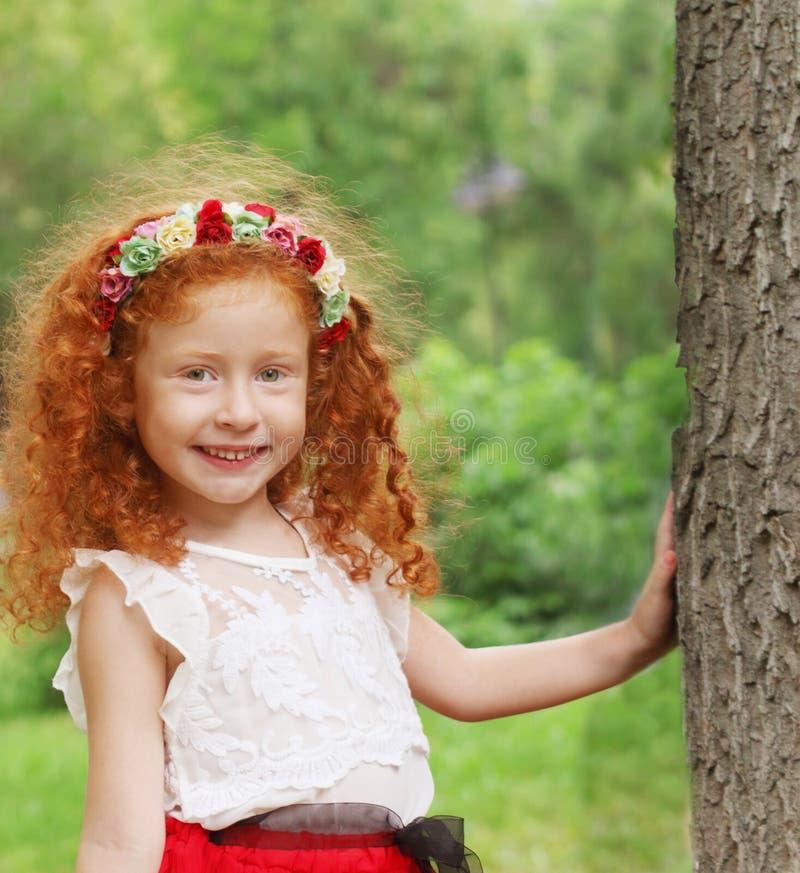 Petite fille avec des supports de guirlande de fleurs photographie stock