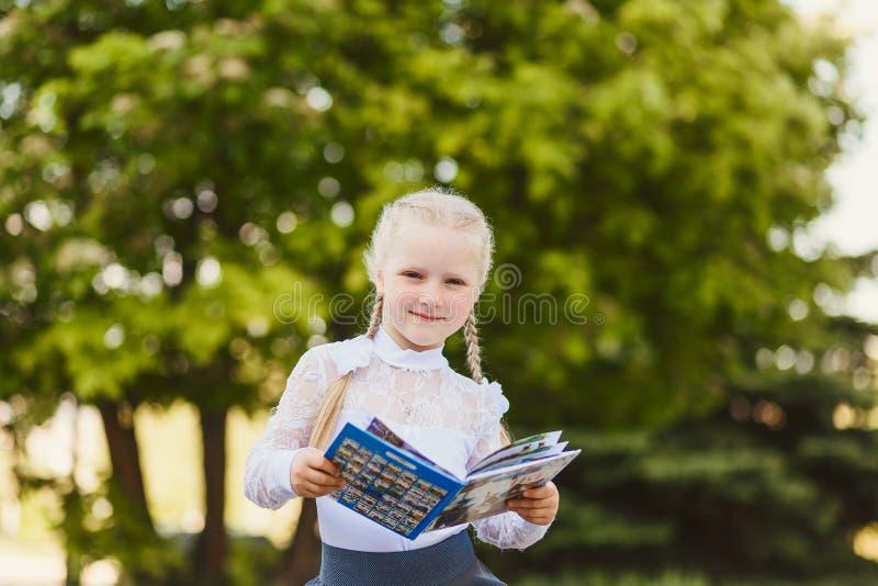 Petite fille avec des tresses lisant un livre dehors images stock