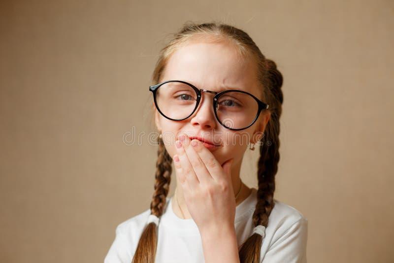 Petite fille avec des verres dans un T-shirt blanc photographie stock libre de droits