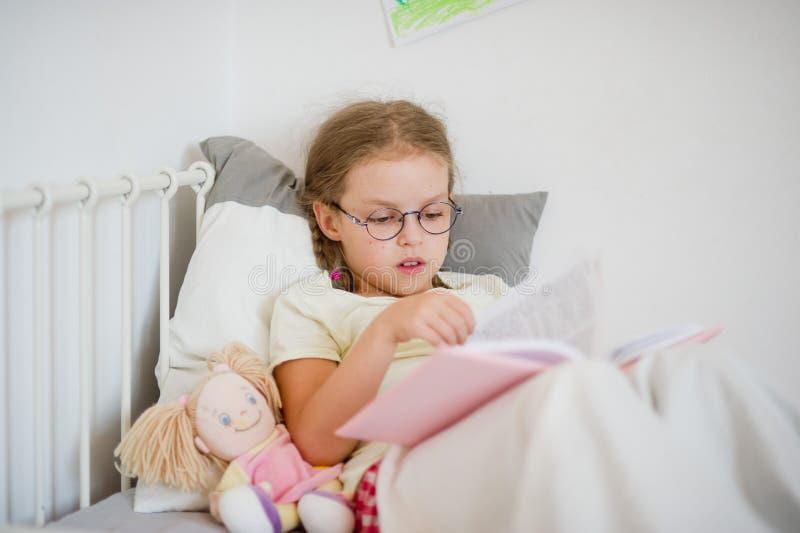 Petite fille avec des verres poussant des feuilles par un livre tout en se situant dans le lit photo libre de droits