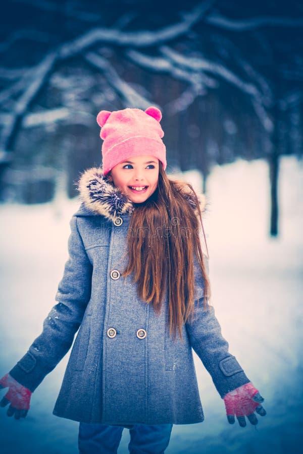 Petite fille avec du charme dans une neige photo libre de droits