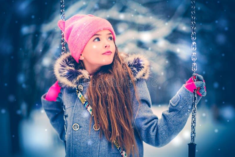 Petite fille avec du charme sur l'oscillation en hiver neigeux photos stock