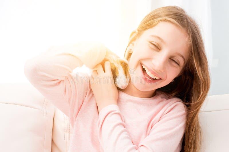 Petite fille avec du charme tenant le cobaye près de sa joue image libre de droits