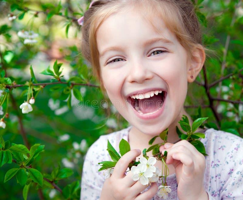 Petite fille avec l'arbre de floraison de buisson image stock