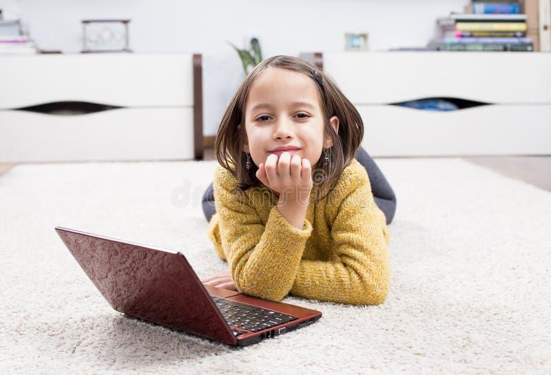 Petite fille avec l'ordinateur portable image stock