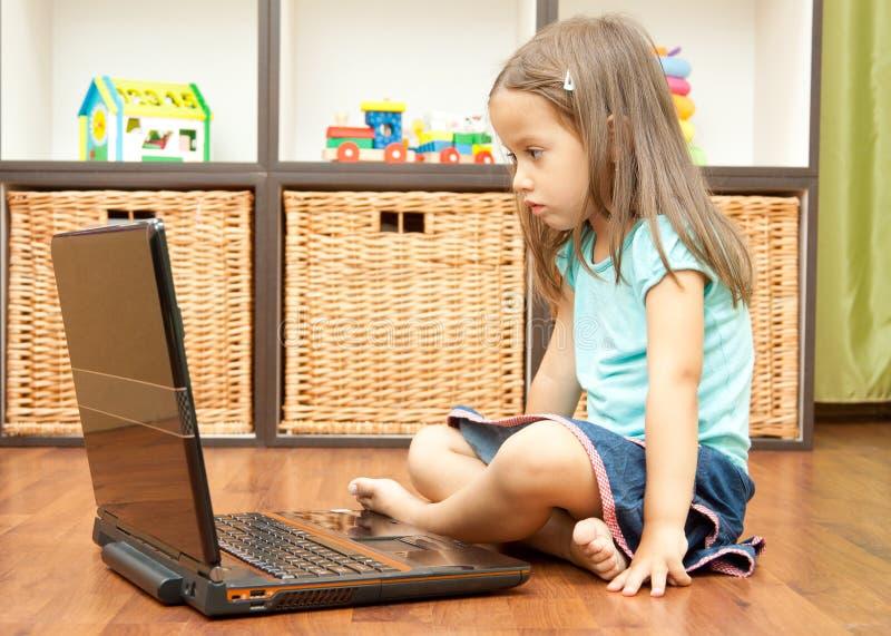 Petite fille avec l'ordinateur portatif photographie stock libre de droits