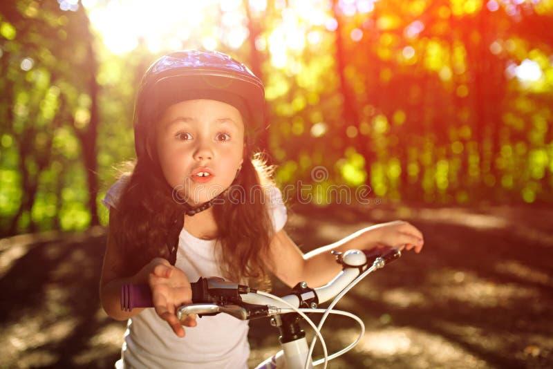 Petite fille avec la bicyclette en parc d'été contre le coucher du soleil photos libres de droits
