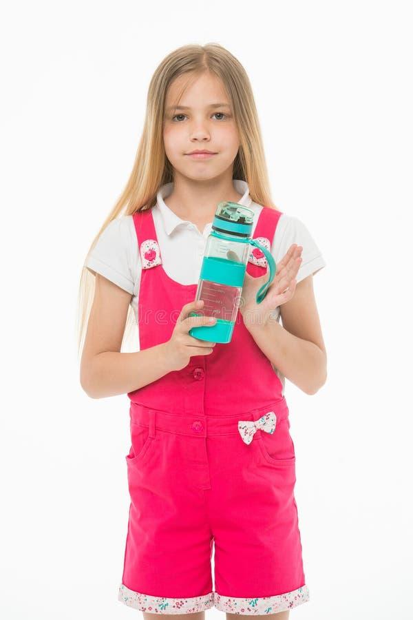 Petite fille avec la bouteille en plastique d'isolement sur le blanc Enfant assoiffé dans la bouteille d'eau rose de prise de sal image libre de droits
