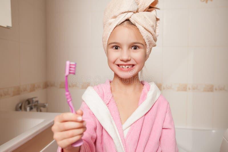 Petite fille avec la brosse à dents à disposition photographie stock