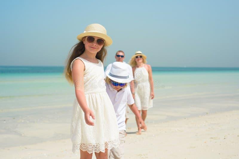 Petite fille avec la famille marchant le long d'une plage images stock