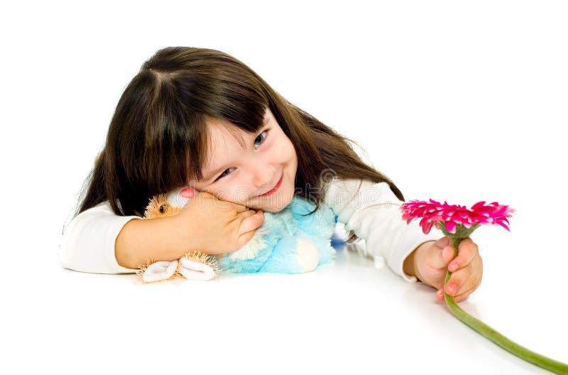 Petite fille avec la fleur rouge de gerber. d'isolement images stock
