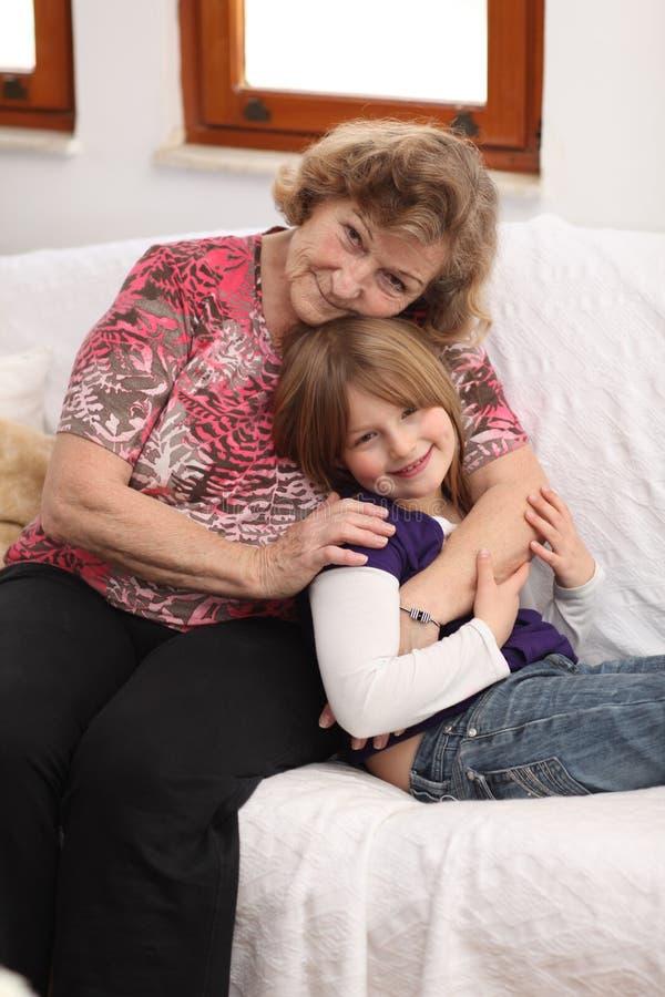 Petite fille avec la grand-mère sur le sofa images libres de droits