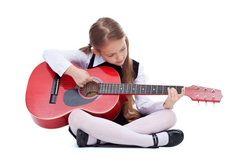 Petite fille avec la guitare rouge, se reposant photo libre de droits