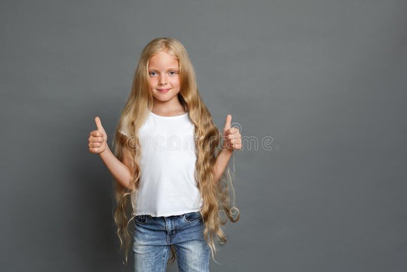 Petite fille avec la longue position de cheveux d'isolement sur les pouces gris d'apparence vers le haut de gai photos stock