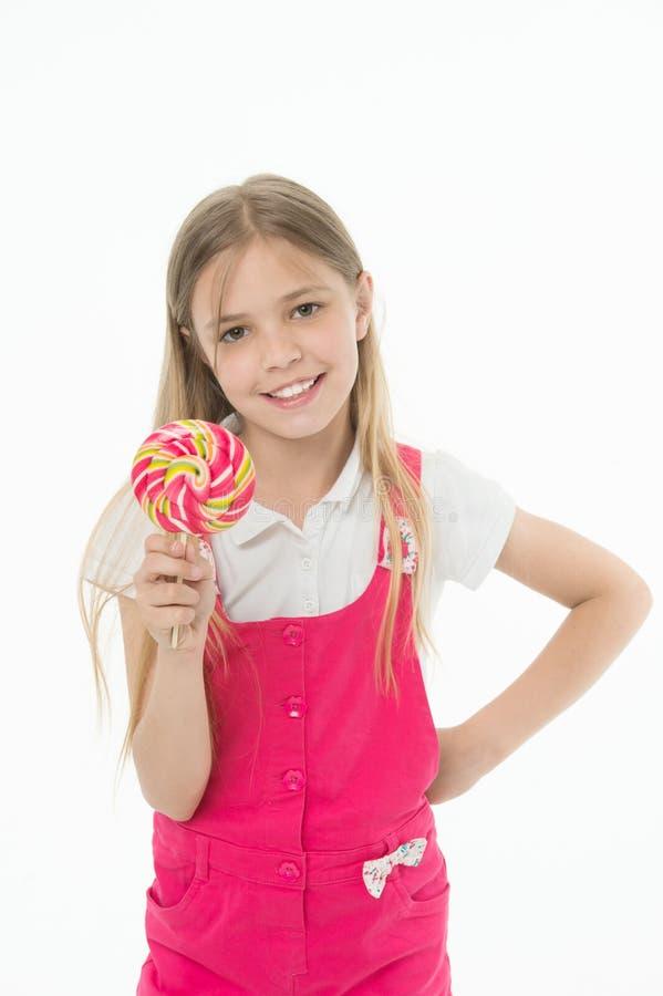 Petite fille avec la lucette Sucrerie de lucette de prise de petite fille sur le bâton Années heureuses d'enfance Elle a un pied  image stock