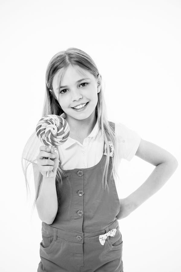 Petite fille avec la lucette Sucrerie de lucette de prise de petite fille sur le bâton Années heureuses d'enfance Elle a un pied  image libre de droits